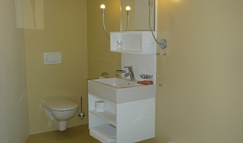 Spacious bathroom with bath, wash basin, mirror and toilet in one of the XL Design apartments